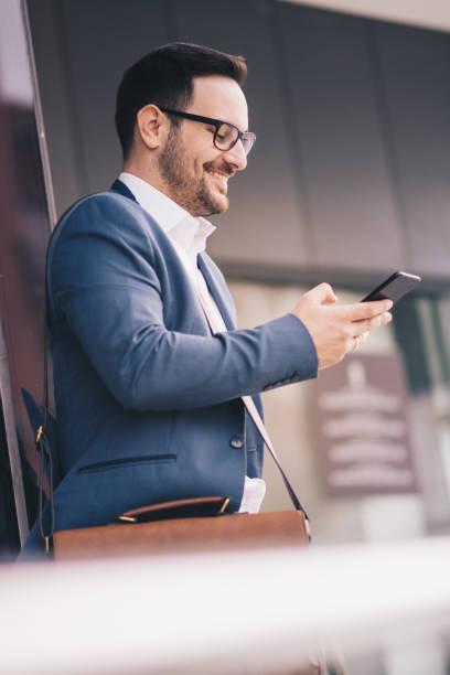 A young man in suit using his phone outdoors. stock photo
