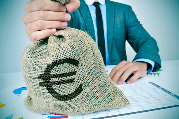 young man in suit with a burlap money bag with the euro sign a young caucasian man wearing a gray suit seated at an office desk full of charts and financial balances holds a burlap money bag with the euro currency sign in his hand euro symbol stock pictures, royalty-free photos & images