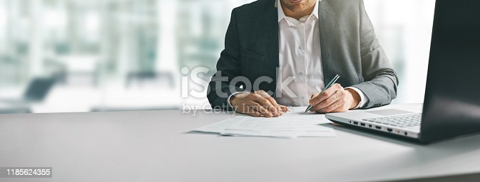 young man in suit writing business papers at desk in modern coworking office. copy space