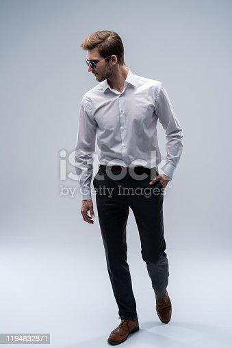 907934274 istock photo young man in sunglasses looks to side while walking on gray studio background. 1194832871