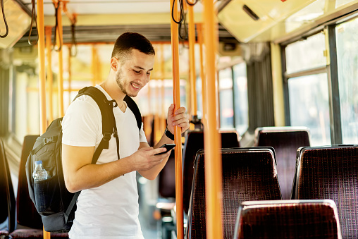 Young Man in the Bus with Smart Phone