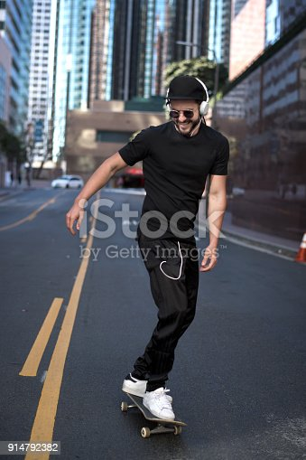 Portrait of young male hipster with headphones while skateboarding in the middle of the street.