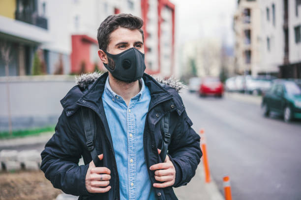 Young man in the city wearing anti-smog mask for health protection stock photo