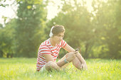 istock Young man in the park listening music 505443731