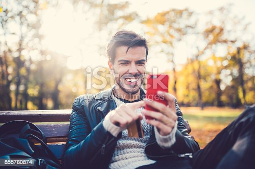 Smiling man sitting at park bench and using smartphone for online payments
