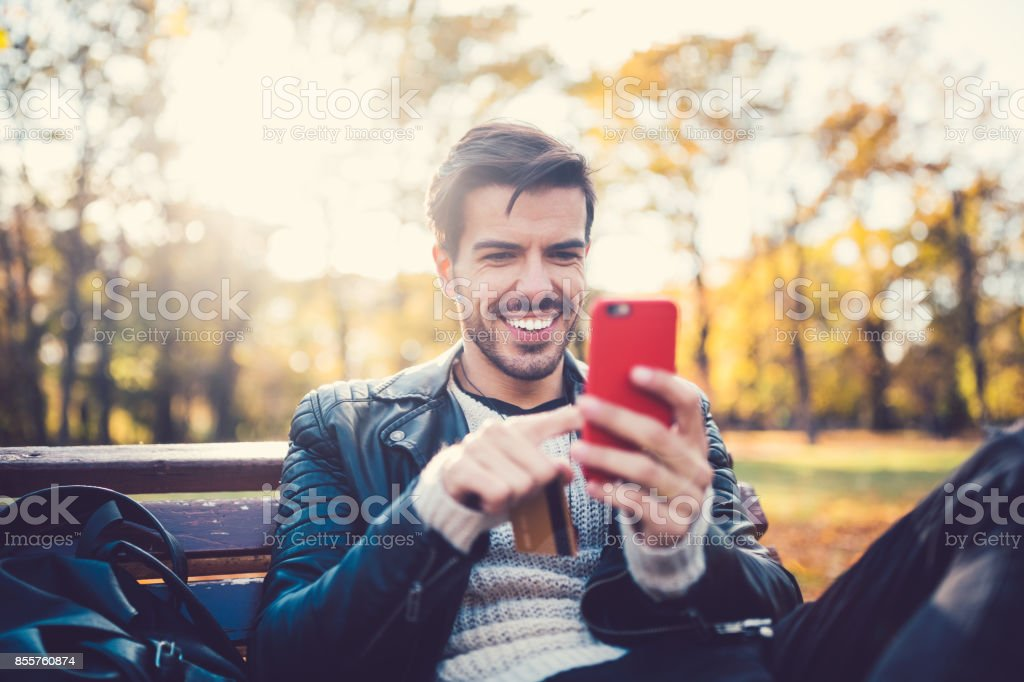 Junger Mann im Park Online-shopping – Foto