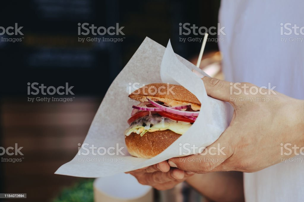 Young man in the white t-shirt holding in hands fast food burger,...