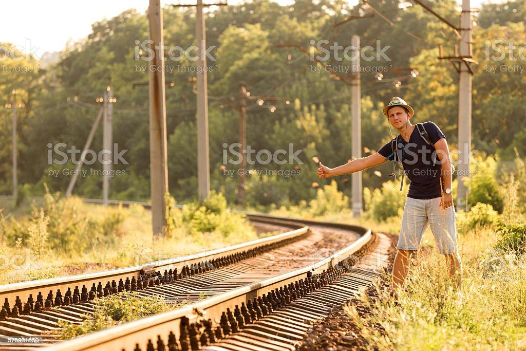 Young Man in Travel Clothing hitch hiking Railroad Train stock photo