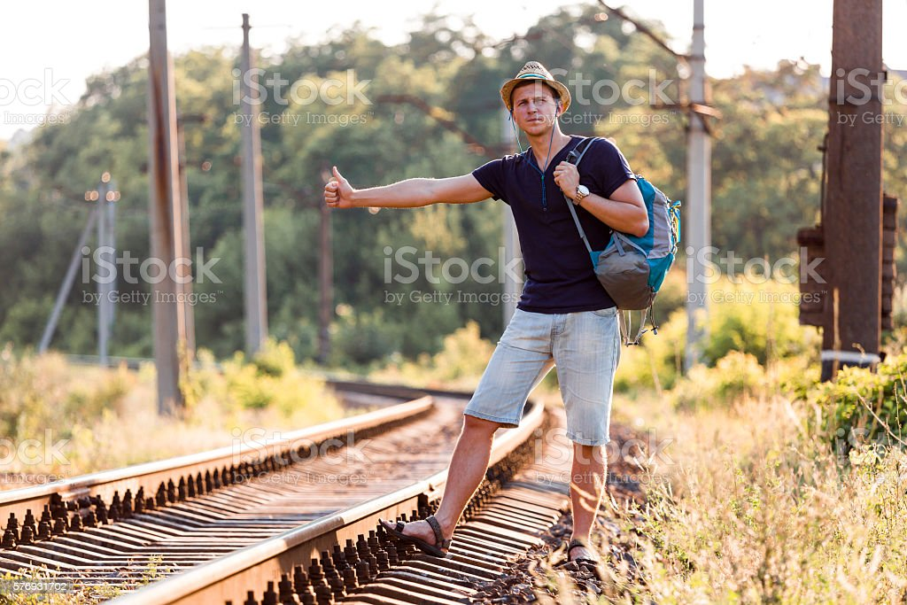 Young Man in Travel Clothing hitch hiking rural Railroad Train stock photo