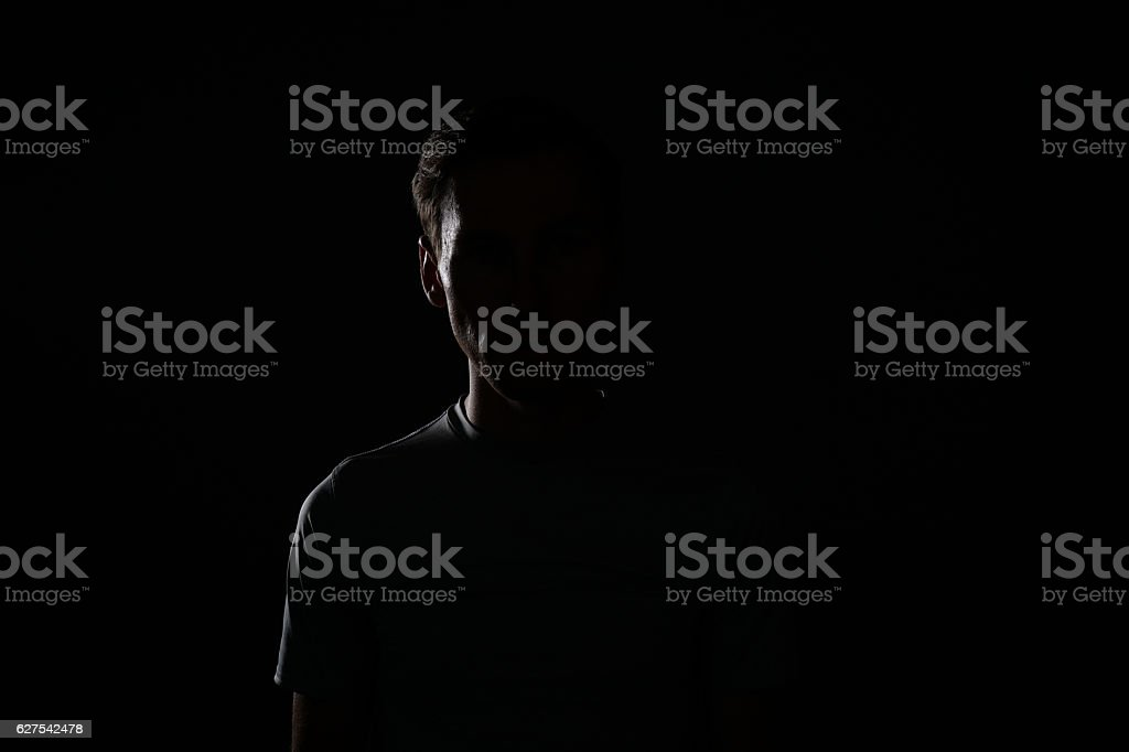 Young man in t-shirt on dark background. stock photo