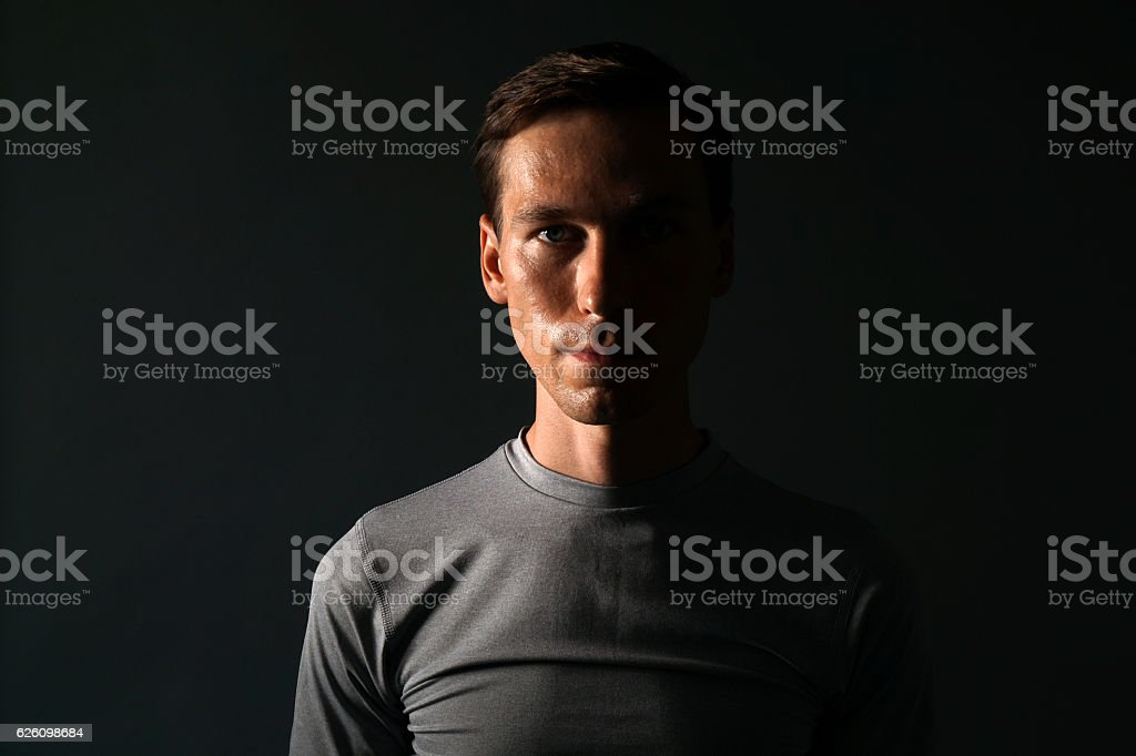 Young man in t-shirt on gray background. stock photo