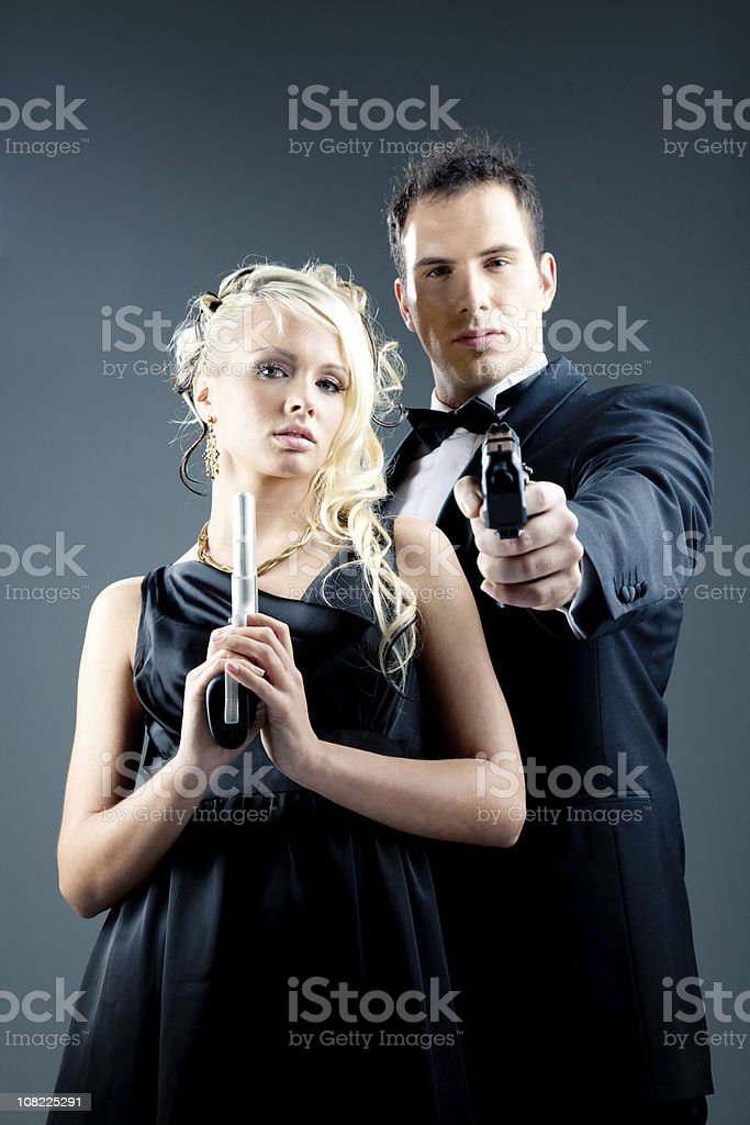 Young Man in Tuxedo and Woman Posing with Guns royalty-free stock photo