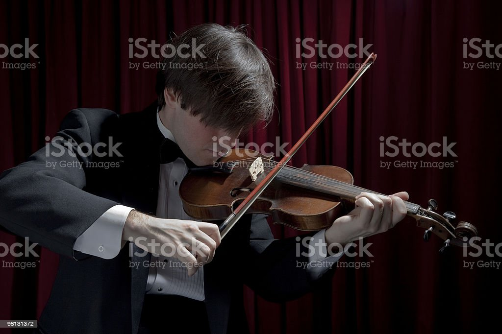 Young man in tuxedo playing violin royalty-free stock photo
