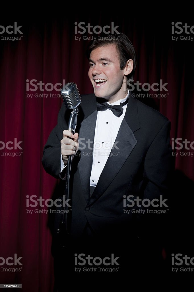 Young man in tuxedo with microphone royalty-free stock photo