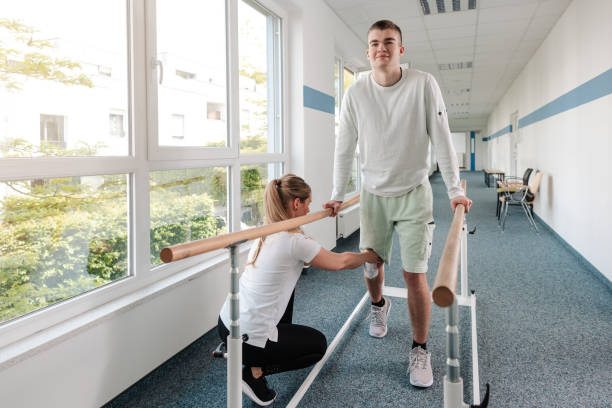 Young man in walking rehabilitation course after a sport injury stock photo