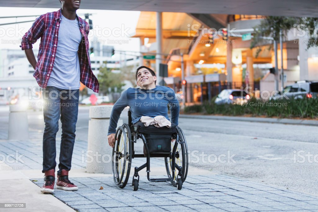 Young man in wheelchair with friend in city stock photo