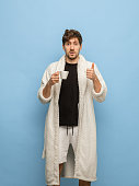 Morning mood. Surprised young man in white bathrobe, home clothing with cup of coffee isolated on blue background. Concept of human emotions, facial expression, home interior. Copy space for ad.