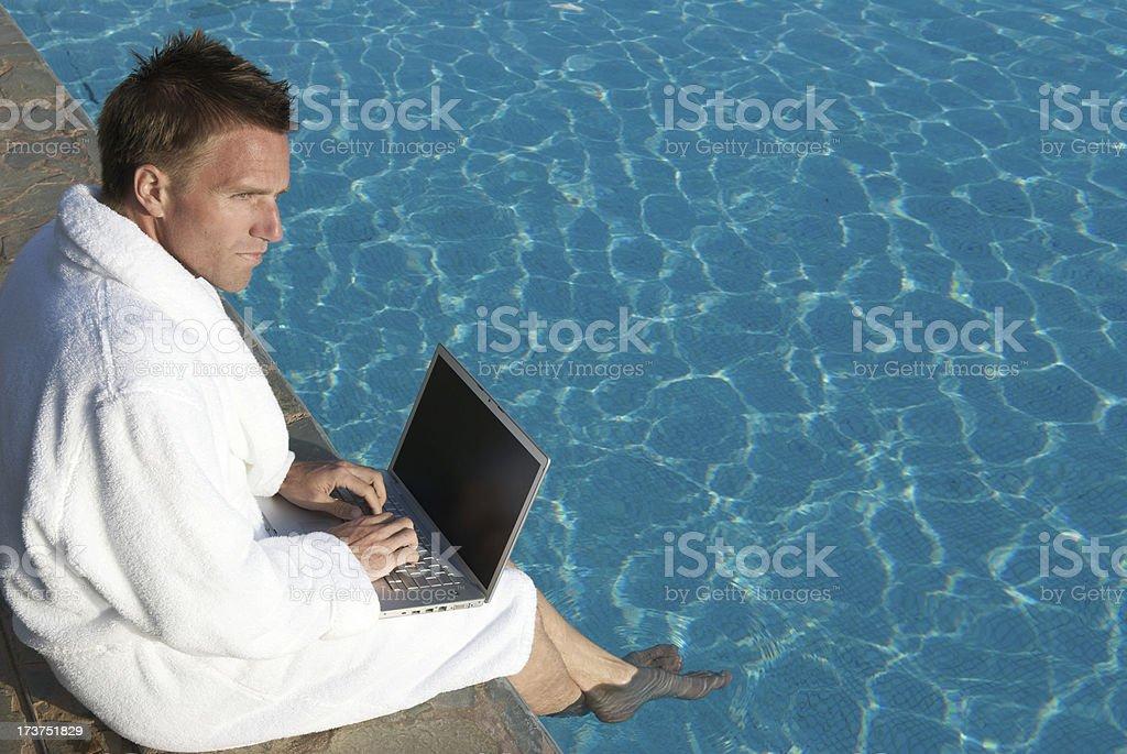 若い男性のホワイトのバスローブを備えたプールサイドにノートパソコン ストックフォト