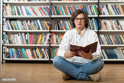 500129038istockphoto young man in white shirt sitting on the floor 499284906