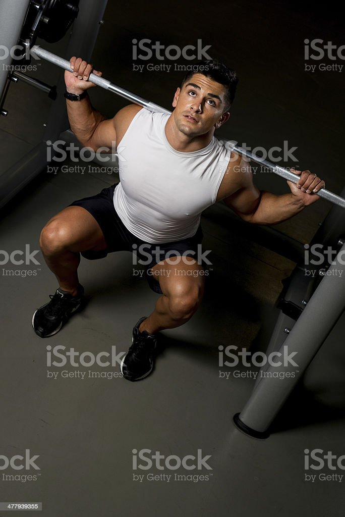 Young man in White T-shirt doing Barbell Squat royalty-free stock photo
