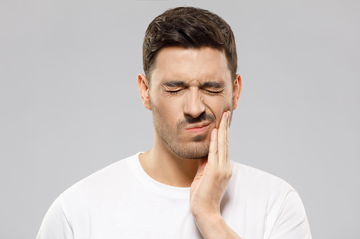 Young man in white t-shirt suffering from severe toothache, touching cheek with fingers, eyes closed because of strong pain, isolated on gray background