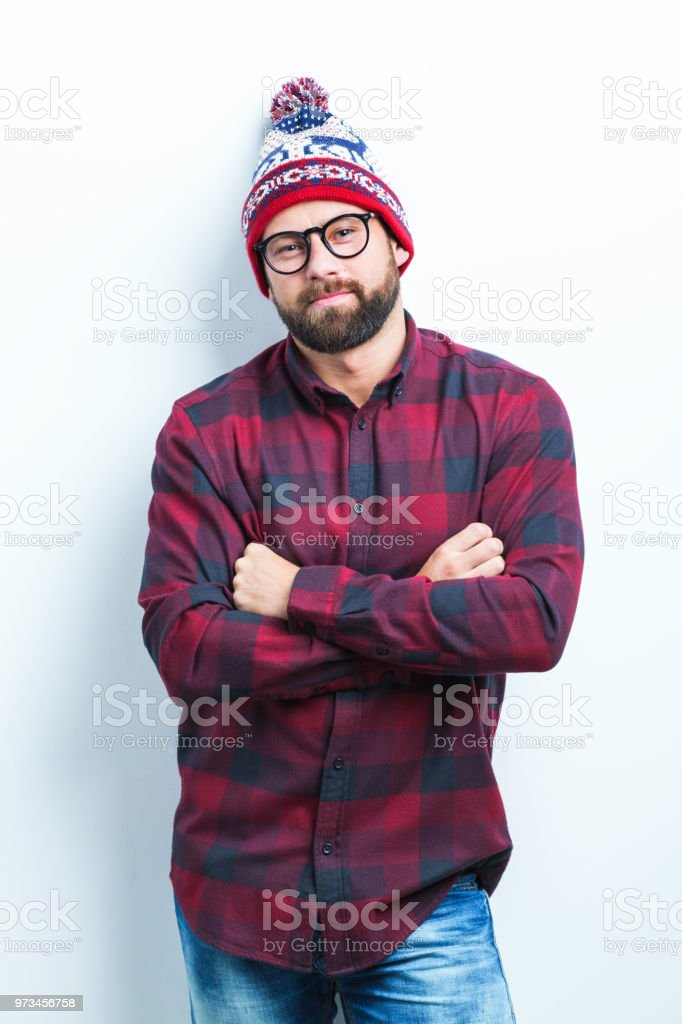 Young man in winter cap Portrait of young man in winter cap standing with his arms crossed on white background Adult Stock Photo