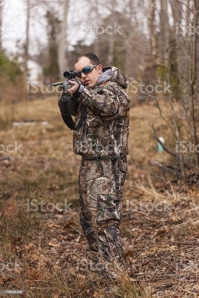 Young man in woods aims rifle royalty-free stock photo