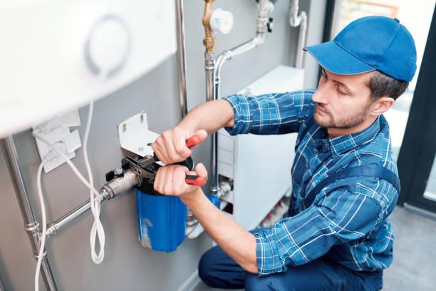 Joven en ropa de trabajo usando alicates mientras instala el sistema de filtración de agua - foto de stock