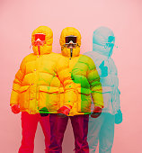 Winter fashion. Collage. Young man in bright yellow puffy jacket isolated over pink background with glitch effect. Concept of emotional, facial expression, funny meme emotions. Copy space for ad.