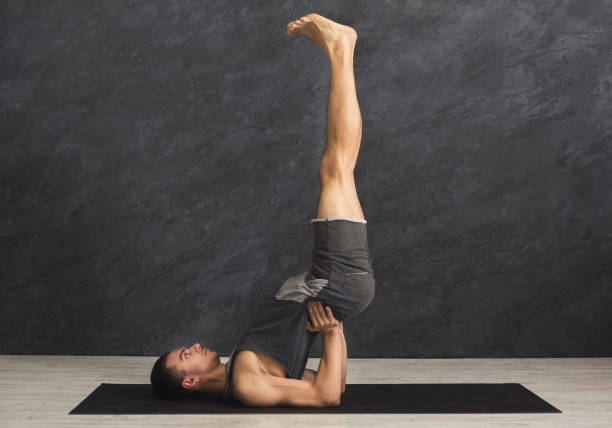 Young man in yoga class doing shoulder stand Young sporty man in yoga class doing shoulder stand. Fitness guy stretching in sarvangasana. Healthy lifestyle in fitness club, copy space shoulder stand stock pictures, royalty-free photos & images