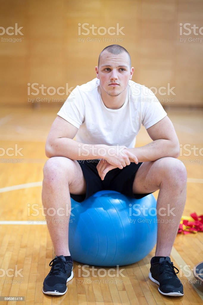 Young Man Indoor Gym Taking a Rest on Equipment royalty-free stock photo