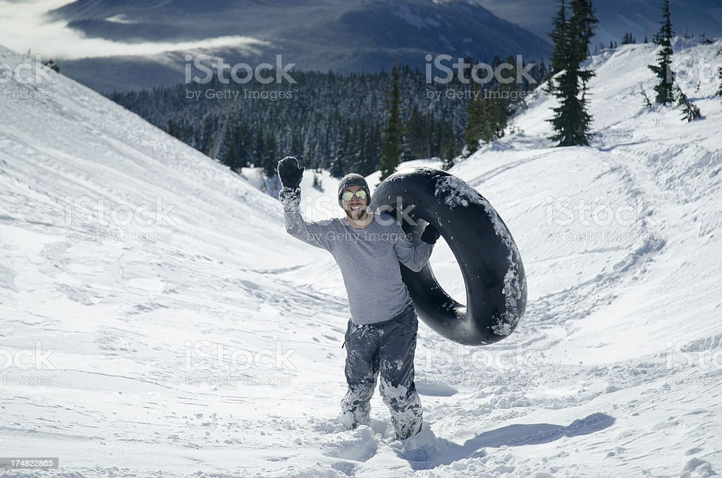 Young Man Inner Tubing in the Snow stock photo