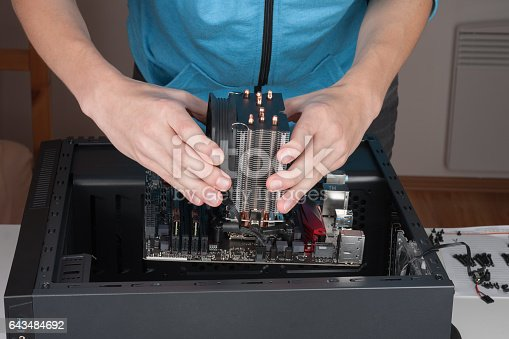 istock Young man insert ATX motherboard to computer case 643484692