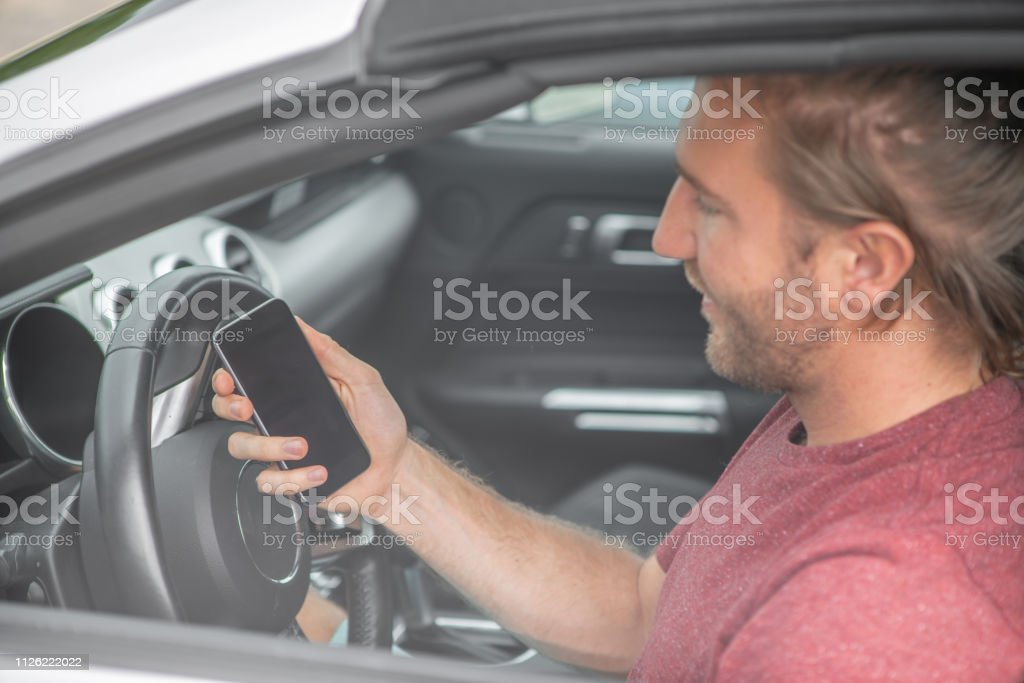 Caucasian male sitting in car at the steering wheel using mobile phone