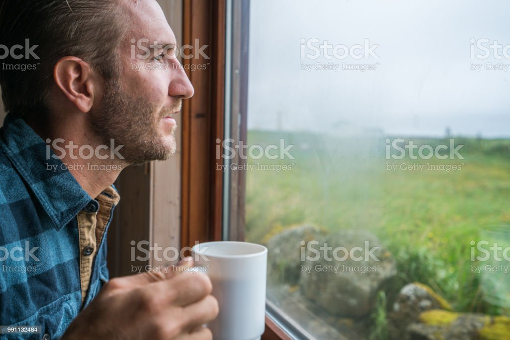 Cheerful young man in the morning drinking coffee inside guest house...