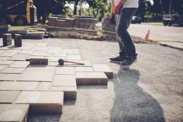 Young man installing paving stones for a new driveway stock photo