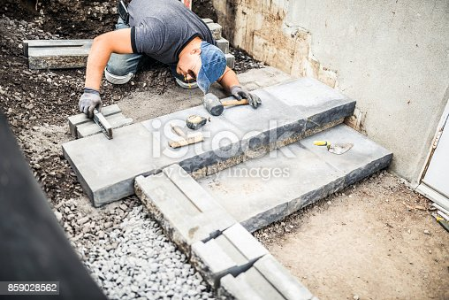 istock Young man installing paving stones 859028562