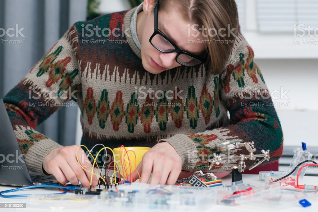 Young man intently working with electronic parts stock photo