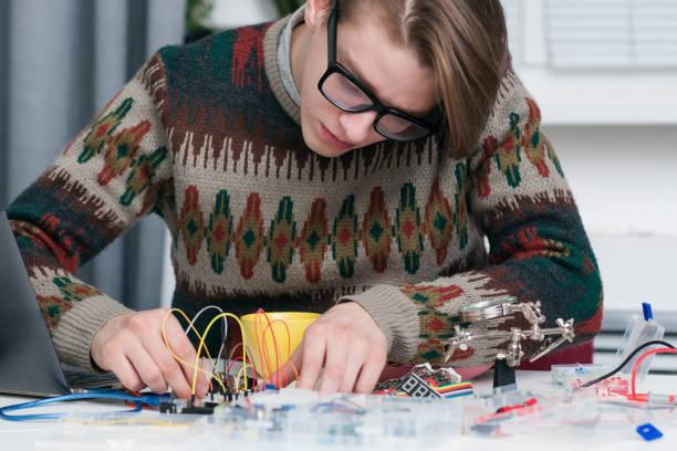 Junger Mann aufmerksam arbeiten mit elektronischen Bauteilen – Foto