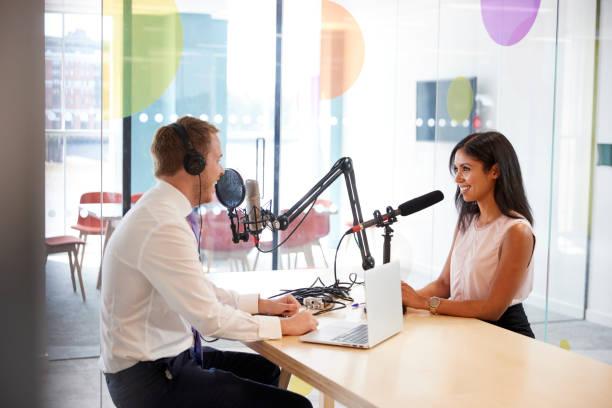 jonge man die een vrouw in een radiostudio interviewen - podcast stockfoto's en -beelden