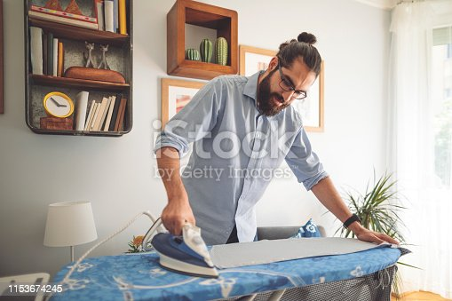 Young man ironing his shirt
