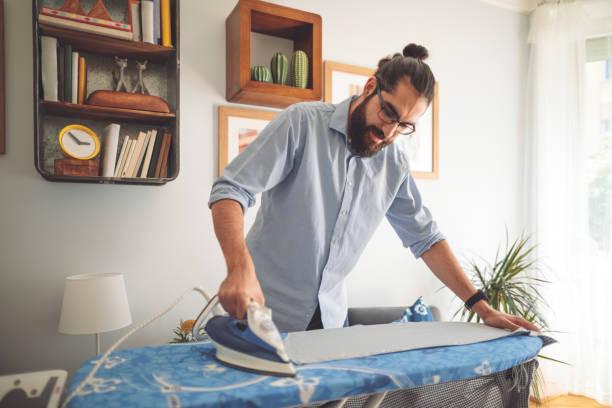 Young man ironing his shirt stock photo