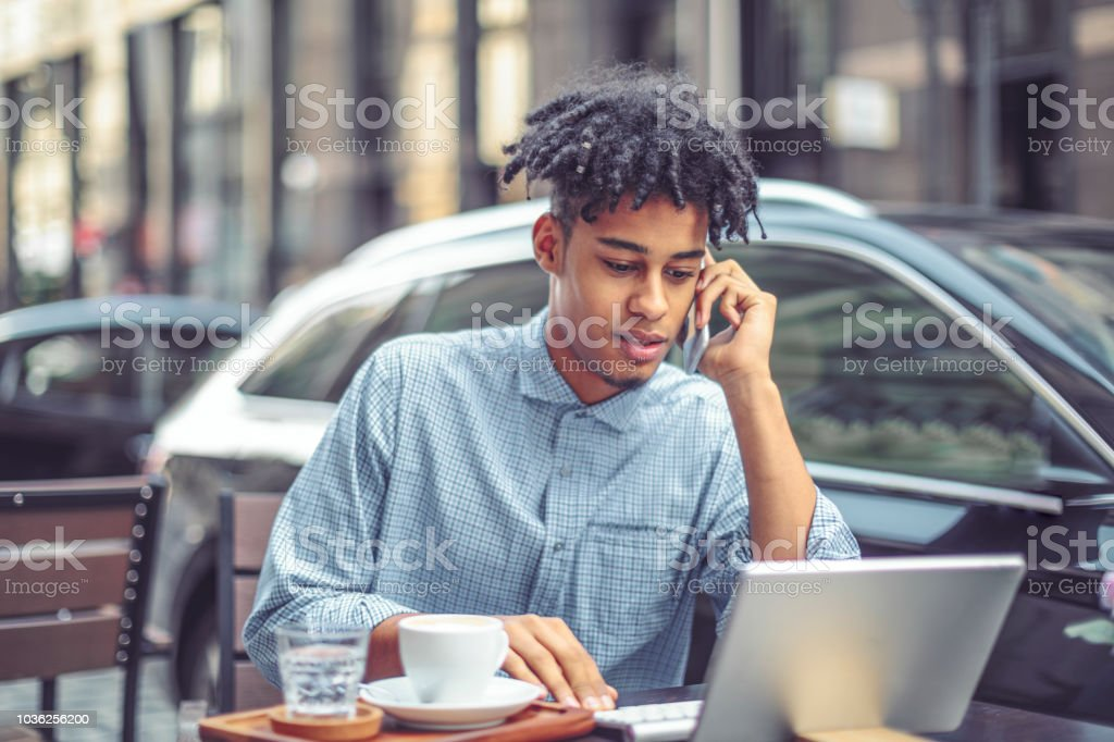 Young man is blogging from a sidewalk caffee stock photo