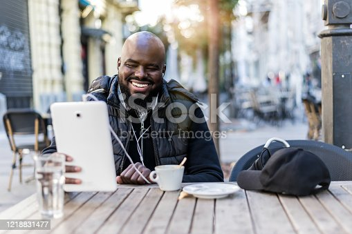 544356862 istock photo Young man is blogging from a sidewalk caffee 1218831477