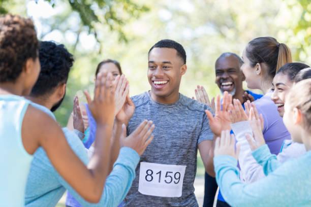 junger mann wird mit hohen fünfer nach rennen gratulierte. - laufveranstaltungen stock-fotos und bilder