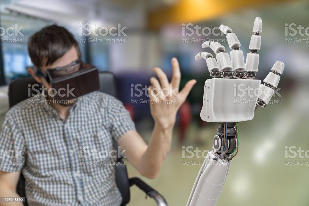 Junger Mann steuert Roboterhand mit virtual-Reality-Kopfhörer. Lizenzfreies stock-foto