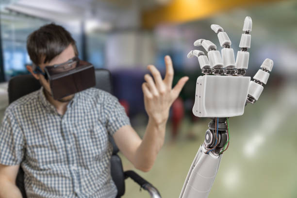 Young man is controlling robotic hand with virtual reality headset. stock photo