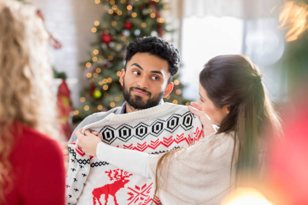 Young man is disappointed with new Christmas sweater stock photo