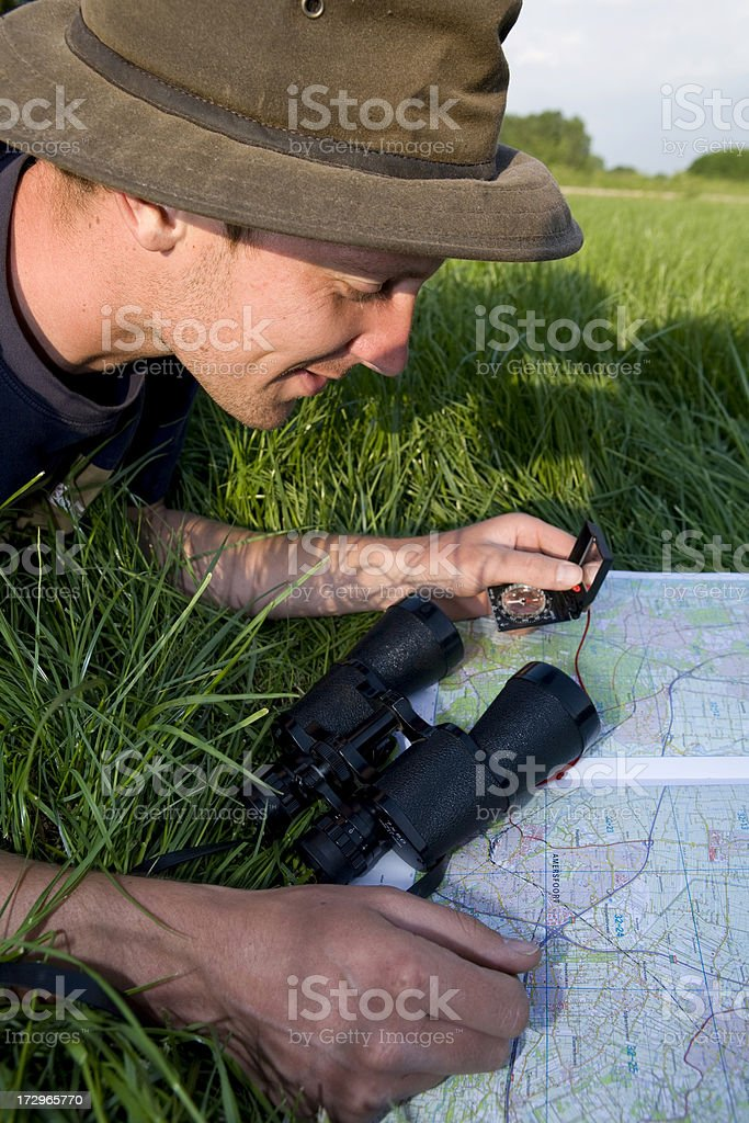 Young man is discovering the map with a compass royalty-free stock photo