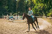 Young man is enjoying horseback riding in nature